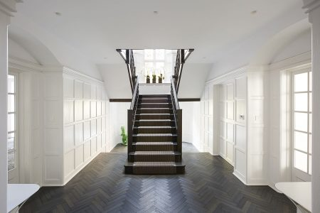 Generous entrance hall with timber staircase of Arts-and Crafts residence