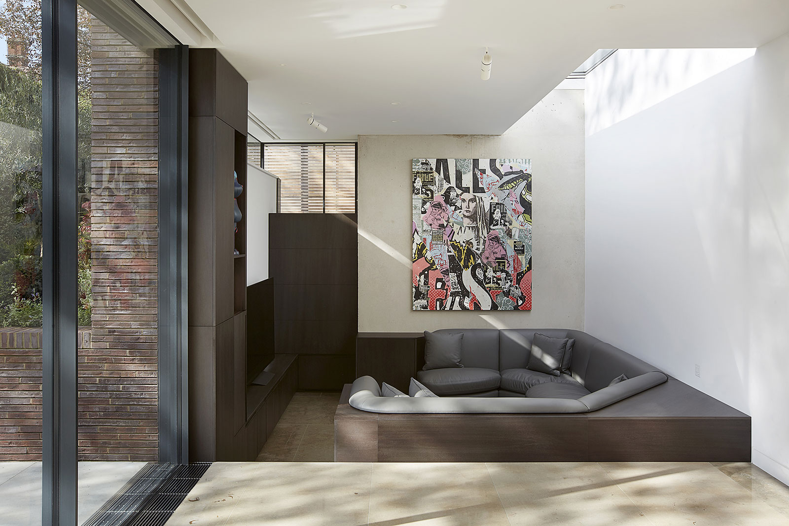 contemporary interior featuring fair faced concrete wall, sunken seating area and large windows