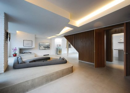Contemporary interior featuring concrete floor, sunken seating area, brick walls and timber cladding