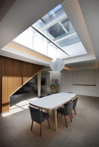 contermporary interior featuring dining table underneath large skylight