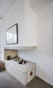 Contemporary interior featuring modern fire place and white washed brick walls
