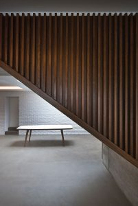 Contemporary interior featuring concrete floor, timber cladding and dining table